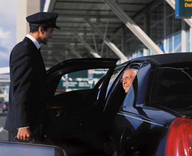 Chauffeur Holding a Suitcase and Opening a Door For a Mature Businessman